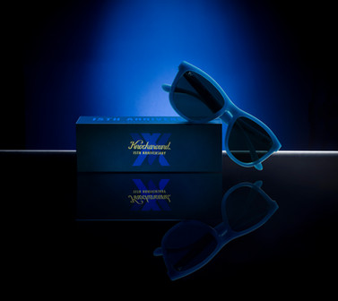 A feature product shot of special edition Knockaround glasses on a black mirrored surface with a vibrant blue background
