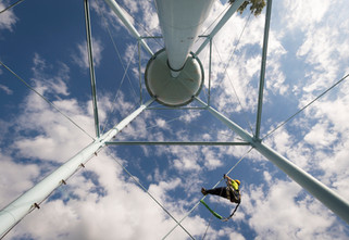 A tower climber scales a water tower against big blue skies to rig industrial equipment.