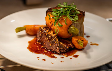 A savory beef dish accented with vibrant carrots and lush green garnish