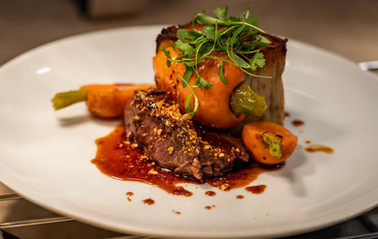 Tantalizing food photography: a savory steak medallion with garnish, carrots, and sauce.