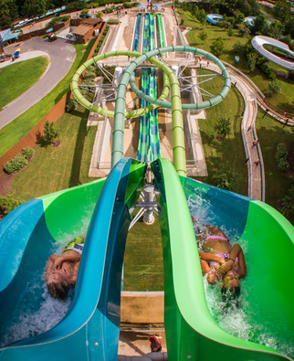 Kids plunge down the massive and colorful drop slide, Vanish Point, at Water Country USA in Williamsburg, Virginia.