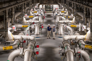 Employees stand in the middle of a massive industrial and architecturally symmetrical pipe room discussing a project.