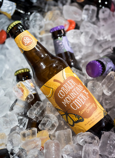 Tantalizing food photography of different flavors of bottled Cobbler Mountain Cider over a bed of ice