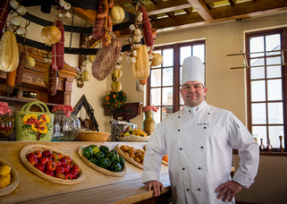 A chef in full uniform poses for a portrait in a European kitchen with hanging meats and bushels of vegetables