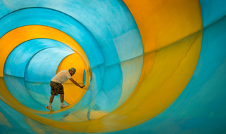 Creative portrait of a construction worker manufacturing a massive blue and yellow water slide.
