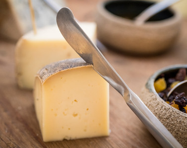 An artisanal cheese block rests among a tasty charcuterie board that includes dried fruits