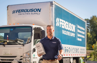 A jovial delivery driver walks away from his box truck to deliver Ferguson products to his customer