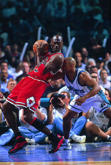 Michael Jordan of the Chicago Bulls backs down a Charlotte Hornets player in NBA playoff action shot for Sports Illustrated.