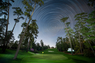 A landscape astrophotgraphy image featuring star trails over the towering trees and lush greens and of Augusta National Golf Course.