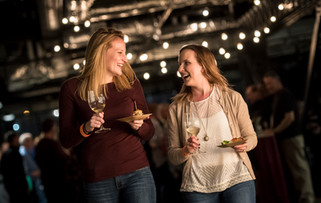 A lifestyle image of two young women laugh to each other as they walk through a bistro with their fine wine and appetizers.
