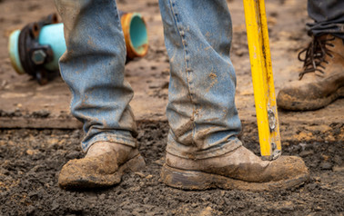 A detail feature of a construction worker and his tools in the mud on an industrial job site.