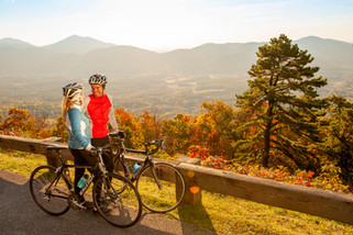 A tourism advertisement of a young couple stopping on their bikes to enjoy a beautiful mountain vista in Virginia.