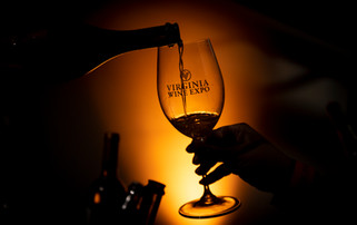 A sommelier pours wine into a backlit wine glass at the Virginia Wine Expo