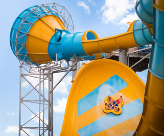 A raft of riders flies up the peak of Colossal Curl, a water slide thrill ride at Water Country USA in Williamsburg, Virginia.
