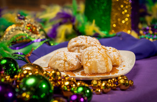 A Mardi Gras themed table featuring a scrumptious looking plate of beignets.