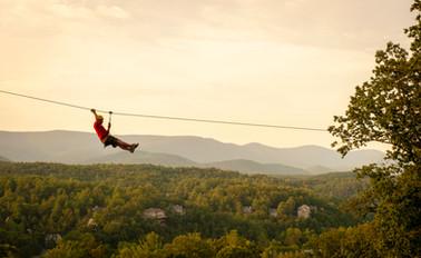 A recreational lifestyle advertisement of a man ziplining against the golden skyline of Virginia's Blue Ridge Mountains.