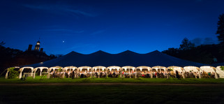 A large outdoor event takes place under the deep blue night sky in Williamsburg, Virginia.