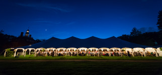 A large outdoor dinner event takes place under the deep blue night sky in Williamsburg, Virginia.