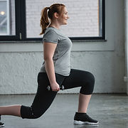 Plus size woman performing lunges with d