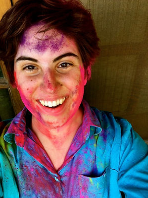 Brianna taking a photo being covered in pin and purple paint