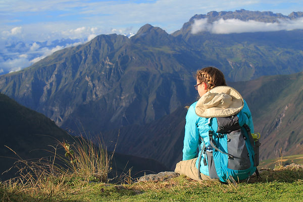 Student sitting in front of mountains