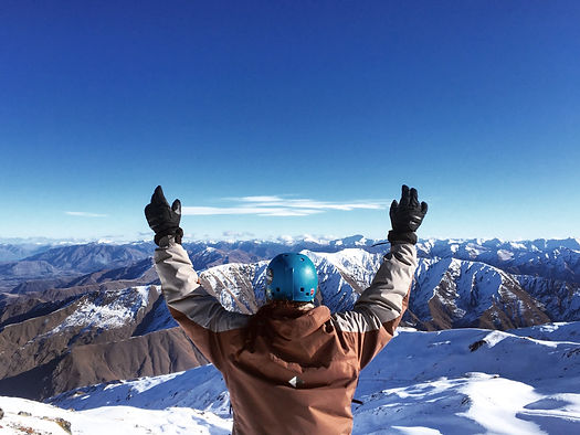 Student with hands raised in front of mountains