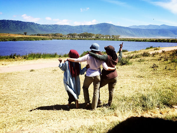 Students posing for a photo in front of a lake