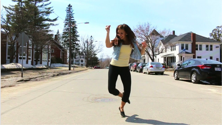 UMF student jumping in a street.