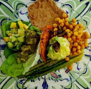 A plate with saute asparagus, avocado mango salad, grilled chicken, tofu with spinach, and wheat naan bread.