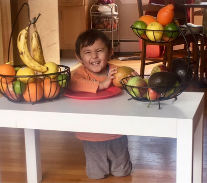 A 3 year old with fruits and vegetables