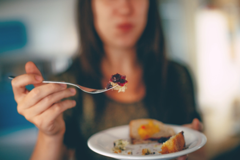 woman holding a forkful of food