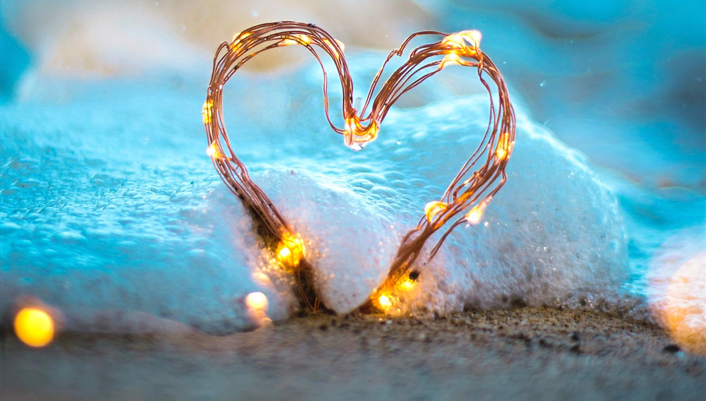 ocean wave with a beach, wooden heart, and lights