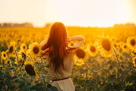 young redheaded woman in a field of sunf
