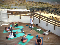 Teaching yoga at the surf villa with the ocean behind