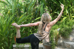 Dancer pose on steps with green jungle behind