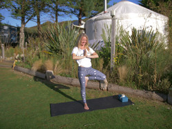 Tree pose in front of a yurt