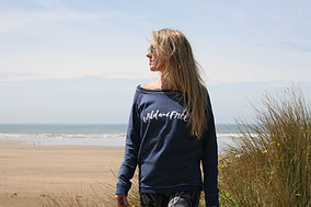 Model wearing navy Wild and Free sweatshirt on the beach