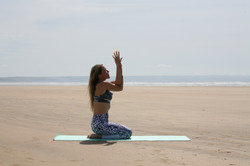 Clasped hands yoga pose on the beach