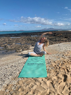 Seated yoga stretch on the beach in Fuerteventura