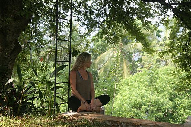 Girl sitting in green jungle in Sri Lanka