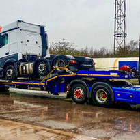 Trucks loaded on extender low loader