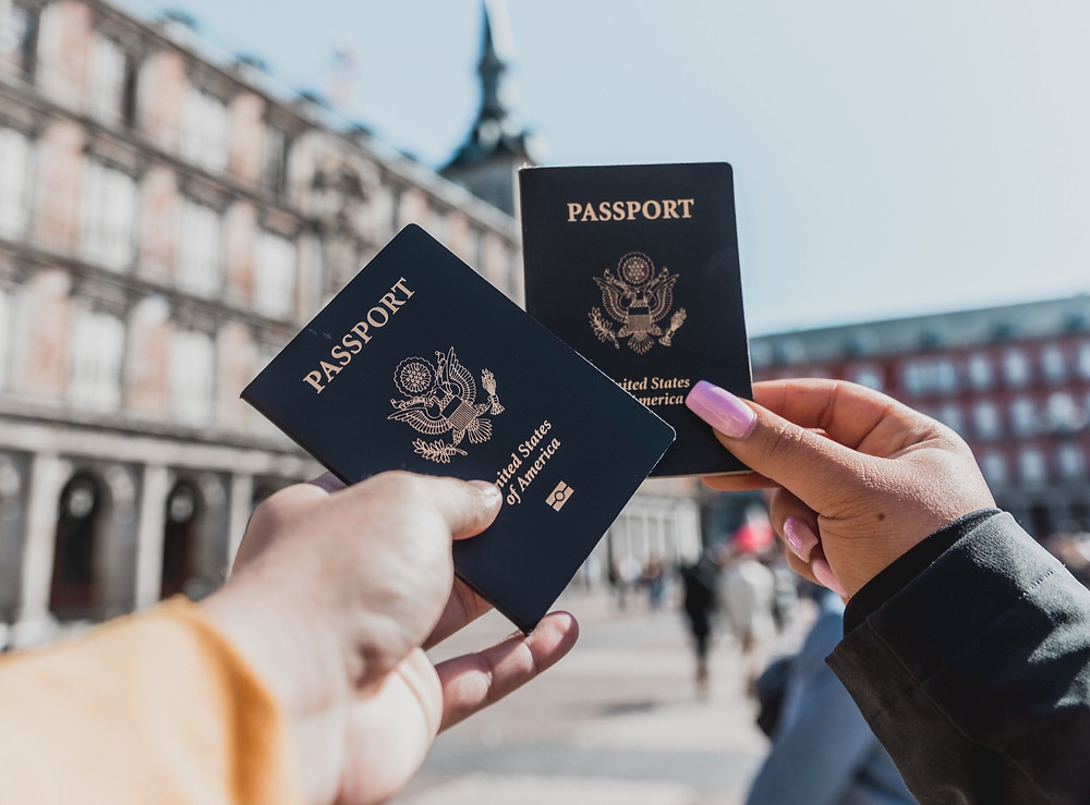 Two US Passports being held into the air for a photo.