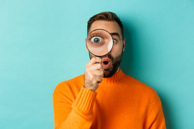 Funny man looking through magnifying glass, searching or investigating something, standing