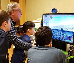 Our students closely follow a lesson on our professional flight simulator!