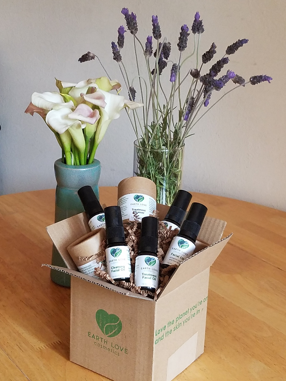 Earth Love Cosmetics products in box with floral displays