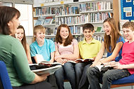 A teacher and a group of six middle-school aged students in a circle with books in a library.