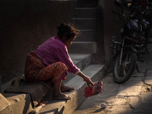 Street photography Nepali woman on stoop in Kathmandu