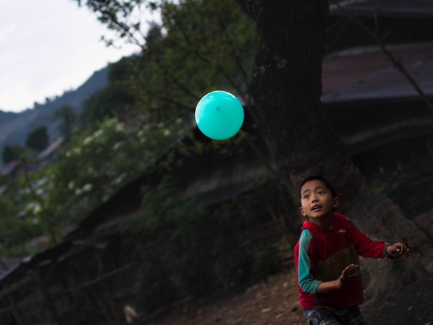 Travel photography boy plays with ballon in Akha Village in Laos