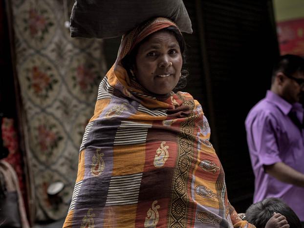 Street photography Nepali mother balances goods on head