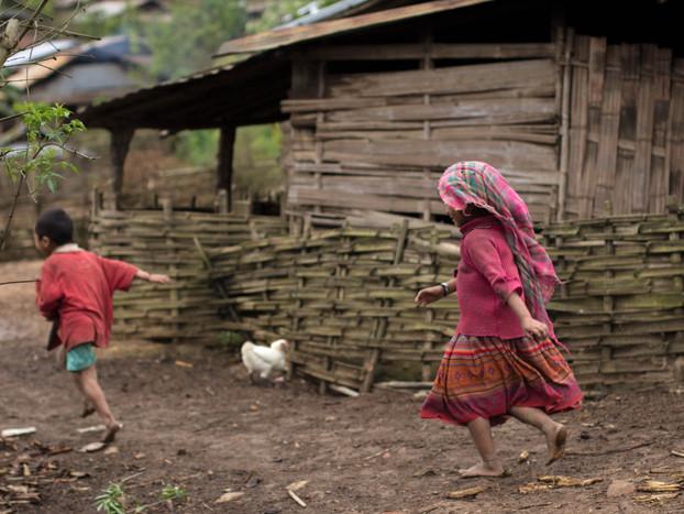 Travel Photography kids chasing in Laos Akha village